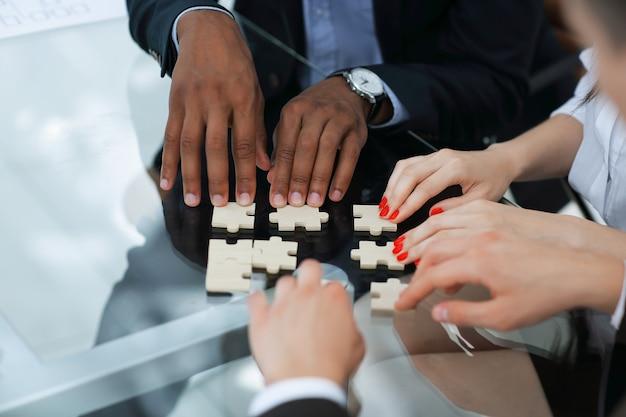 Closeup.business partner, die für die puzzleteile verantwortlich sind. konzept der zusammenarbeit