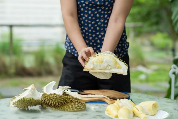Closeup frau hand peeling durian, könig der früchte