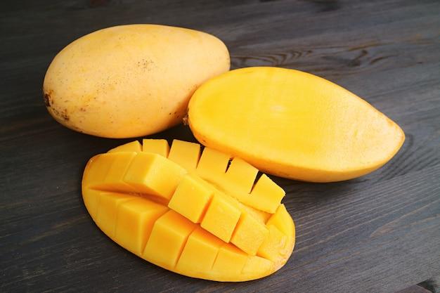 Closeup frische reife saftige mango halbiert und quer geschnitten mit einer ganzen frucht