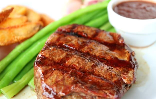 Closeup gegrilltes filet mignon steak mit verschwommenem gedünstetem gemüse und bratkartoffeln im hintergrund