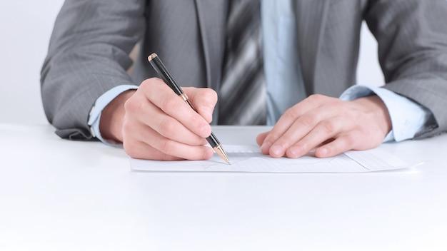 Closeup.geschäftsmann, der mit dokumenten arbeitet, die an einem desk.isolated auf weißem hintergrund sitzen