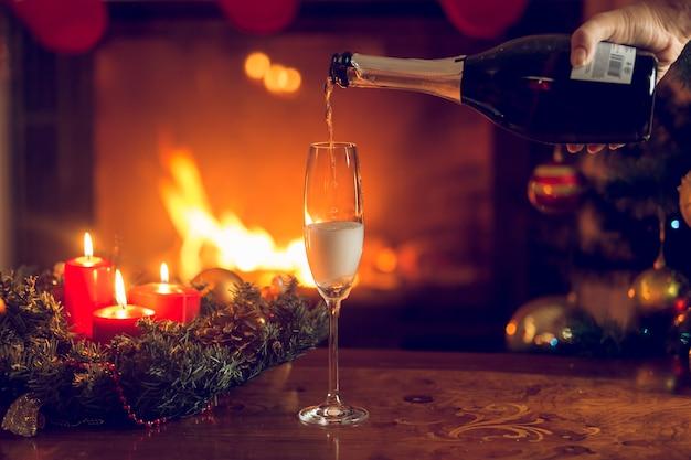 Closeup getönten bild von hand champagner im glas gießen. weihnachtsbaum und brennender kamin im hintergrund