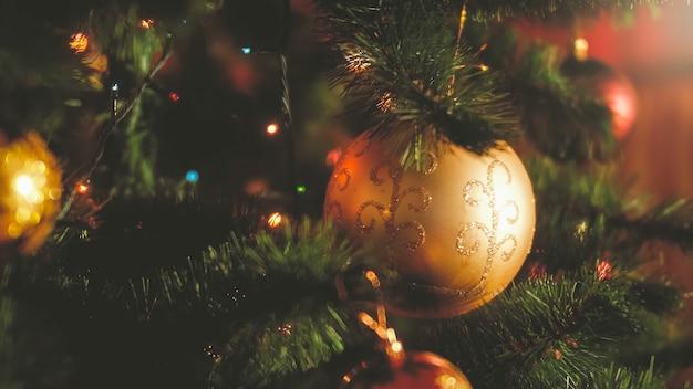 Closeup getönten foto von leuchtenden lichtern und bunten kugeln am weihnachtsbaum im haus. perfekter hintergrund für winterferien und feiern