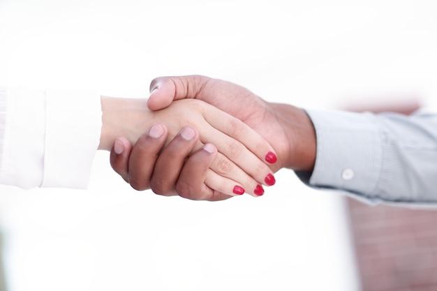 Closeup.greeting geschäftsfrauen mit einem geschäftspartner. das konzept der partnerschaft