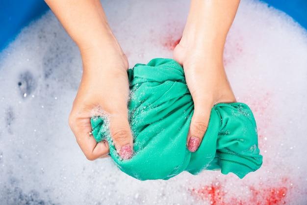 Closeup junge asiatische frau mit hände waschen farbe kleidung im becken