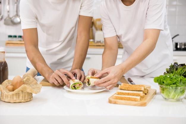 Closeup lgbt homosexuell hände machen sandwich auf küchentisch. gesunder lebensstil für homosexuelle gleichgeschlechtliche familie zu hause.
