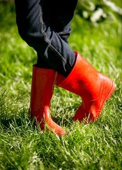 Closeup mädchen in roten gummistiefeln posiert auf frischem grünem gras am sonnigen tag