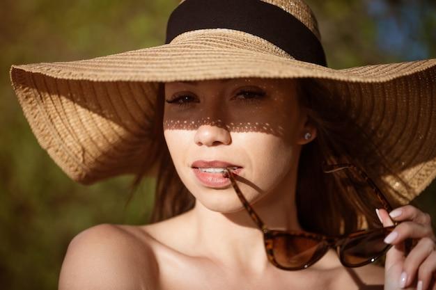 Closeup portrait einer frau mit hut von der sonne an einem sonnigen sommertag schöne kaukasische junge frau...