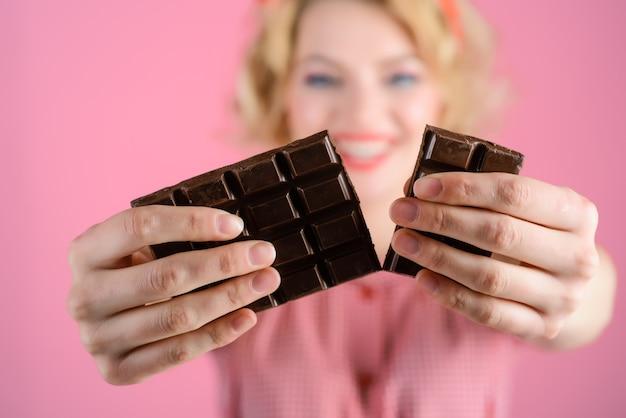 Closeup portrait von pinup girl hält schokolade auf rosa hintergrund nahaufnahme von pin-up lächelnde frau