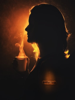 Closeup silhouette eines mädchens mit einem heißen getränk in den händen