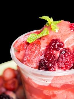 Closeup top von gemischten beerenfrucht smoothies in plastikbecher