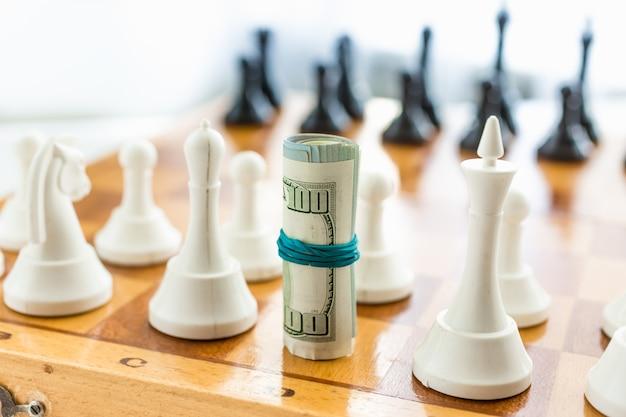 Closeup verdrehtes geld an bord stehen statt schachfigur