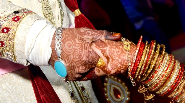 Closup des indischen jungen erwachsenen männlichen bräutigams und der weiblichen braut, die händchen halten