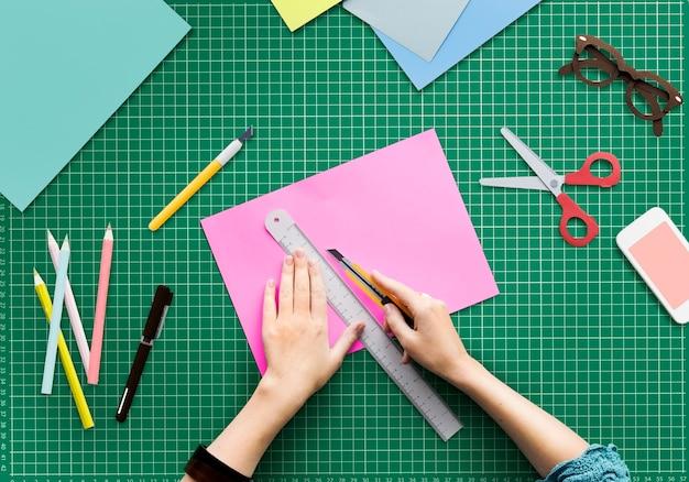 Closup-vogelperspektive von den händen, die papier schneiden