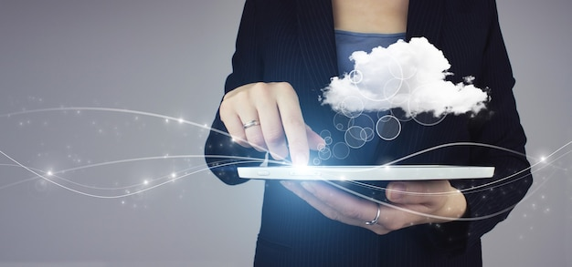 Cloud-computing-technologie-internet-konzept. weiße tablette in der hand der geschäftsfrau mit digitalem hologramm abstrakte wolke zeichen auf grauem hintergrund. abstrakter hintergrund der cloud-verbindungstechnologie.