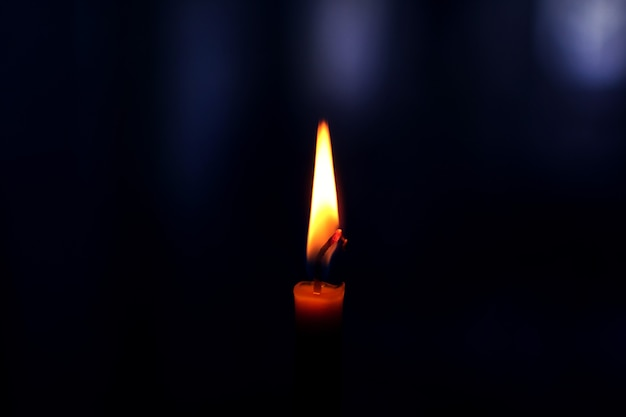 Clouse-up der kerze im dunklen raum. hochwertiges foto
