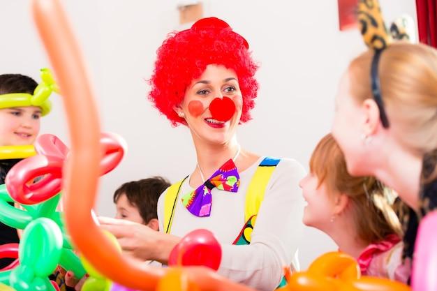 Clown auf kindergeburtstagsfeier, die die kinder unterhält