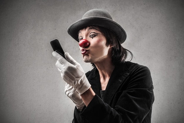 Clown, der einen kuss am telefon sendet