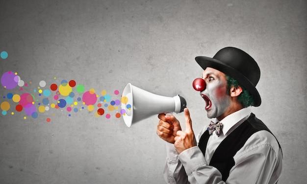 Clown, der in ein megaphon schreit