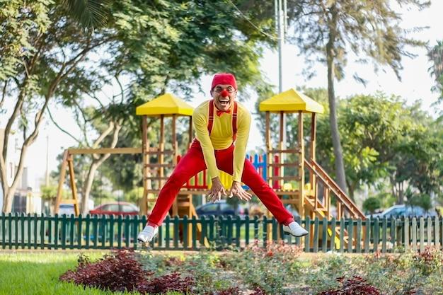 Clown lächelt beim springen in einen park rote hose gelbes hemd