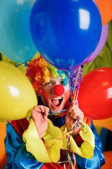 Clown mit einem haufen bunter luftballons.