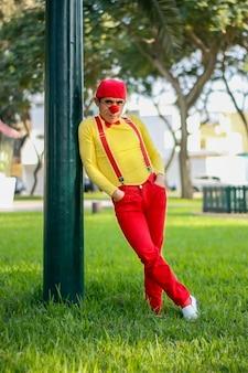 Clown sitzt galant auf einer stange in einem park