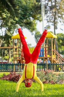 Clown steht auf seinen händen mit gespreizten beinen in einem park
