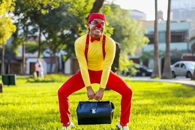 Clown versucht, einen koffer in einem park zu bewegen