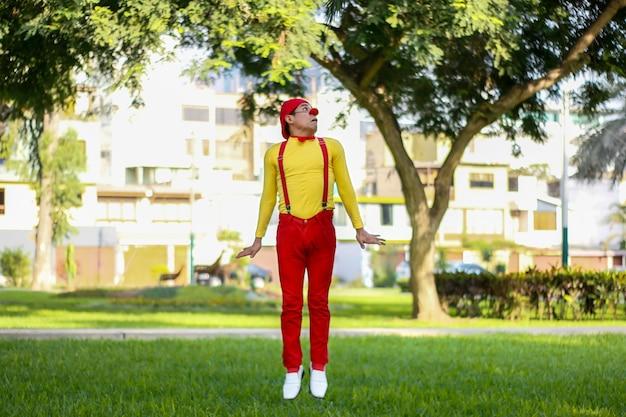 Clown versucht in einen park zu springen rote hose gelbes hemd