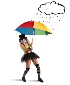 Clowns mit regenbogenschirm, der vor regen schützt