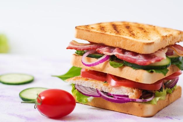Club sandwich mit hühnerbrust, speck, tomate, gurke und kräutern