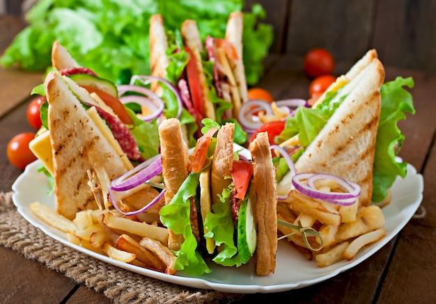 Club sandwich mit käse, gurke, tomate, geräuchertem fleisch und salami. serviert mit pommes frites.