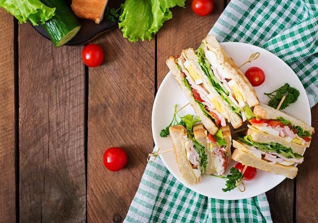 Club sandwich mit käse, gurke, tomate, schinken und eiern. draufsicht