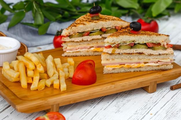Club sandwich mit pommes frites auf holzbrett