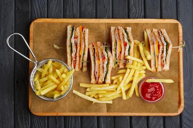 Club-sandwich mit pommes frites im metallkorb