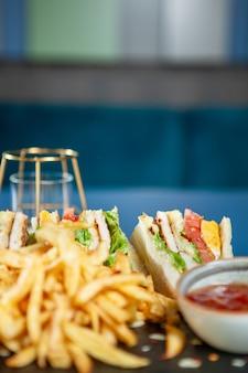 Club-sandwich mit pommes frites mit pfeffersoße .schnelle küche