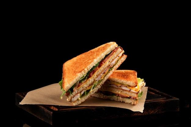 Club sandwich mit schinken, käse, tomaten, sauce, frischem grünem salat mit geröstetem brot.