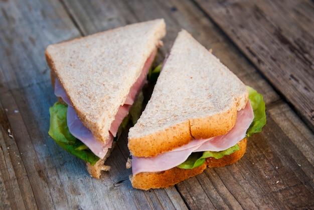 Club sandwich mit schinken und gemüse. rustikales holz.