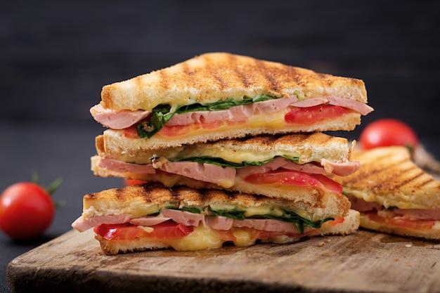 Club sandwich panini mit schinken, tomaten, käse und basilikum.