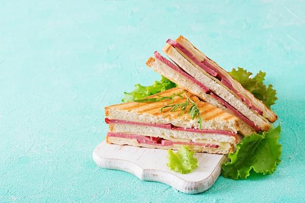 Club sandwich - panini mit schinken und käse auf hellem hintergrund. picknick essen.