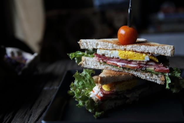 Club sandwiches auf holzhintergrund mit mystischem licht