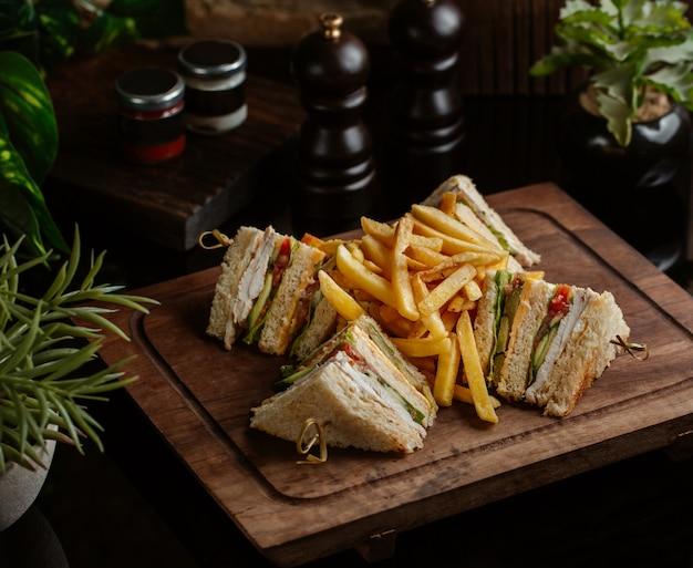 Club sandwiches für vier personen mit pommes frites in einem restaurant mit rosmarinblättern