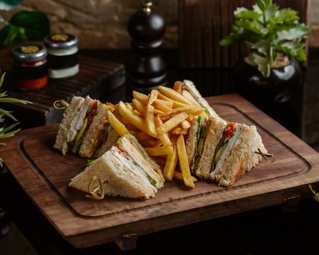 Club sandwiches mit bratkartoffeln auf einem holzbrett