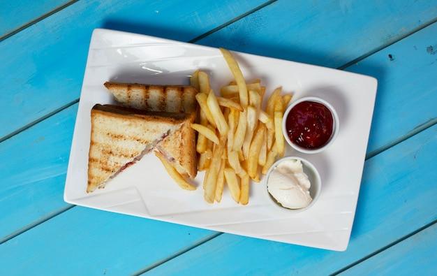 Club sandwiches mit bratkartoffeln und saucen. ansicht von oben.