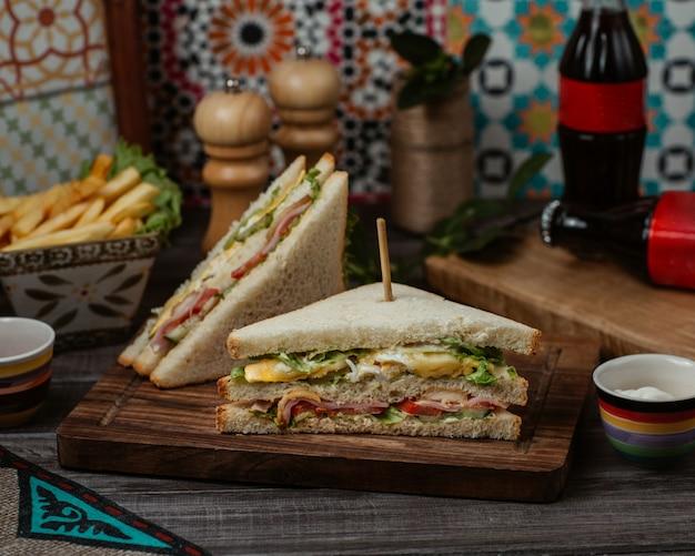 Club sandwiches mit grünem käse und cheddar in weißem toast