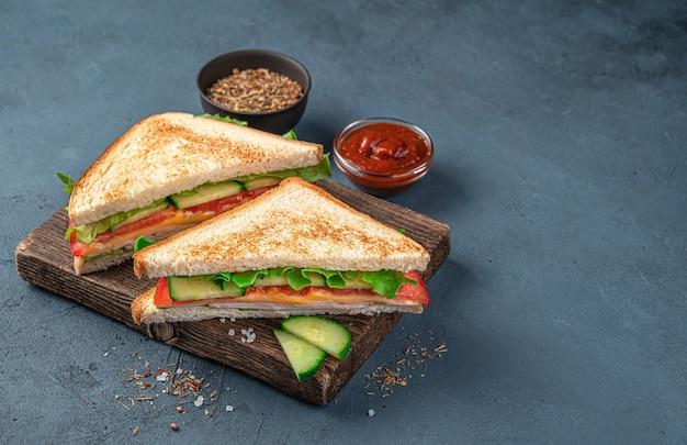 Club sandwiches mit schinken, käse und frischem gemüse auf dunkelblauem hintergrund mit sauce und gewürzen. seitenansicht, kopienraum.