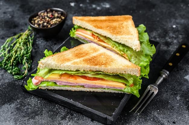 Club sandwiches mit schweinefleischschinken, käse, tomaten und salat auf einem hölzernen schneidebrett. draufsicht.