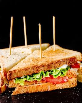 Club sandwiches mit sticks im schwarzen raum.