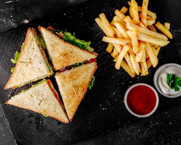 Club sandwiches mit tomatenketchup, mayonnaise und kartoffeln.