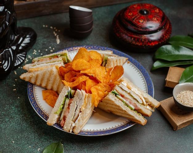 Club sandwiches und kartoffelchips in einer platte.